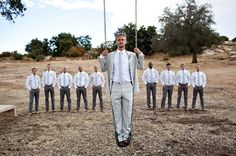 Cute picture of the groom standing on a swing with the groomsmen in the background