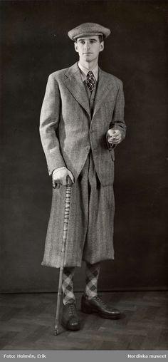 """Nordiska Kompaniet 1931. """"Kläder för sport"""". Man iklädd tredelad kostym med korta byxor, golfrutiga strumpor, keps och käpp. Fotograf: Erik Holmén"""