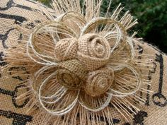 This beautiful handmade flower has four hand rolled burlap flower centers surrounded by layers and sprays of burlap petals. Felt backing. This flower measures approximately 7 inches in diameter and will be perfect as a cake topper for your rustic, woodland or country western themed wedding or event. WIRE FOR CAKE ADDED TO BACK UPON REQUEST. If burlap is what you are looking for, this flower will be an elegant addition! Thanks for stopping by. If you have any questions, please dont…