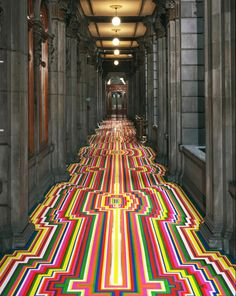 """Visual artist Jim Lambie is well-known for his colorful tape pattern arrangements on the floors of galleries and museums. He uses a simple material like vinyl tape to transform """"a quiet gallery space into an energetic and emotional space of sensory pleasure. Lambie creates a rhythm that vibrates and pulsates, and even confuses and disorients the spectator."""""""