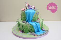 2 tier birthday cake featuring a waterfall and fondant unicorn topper.