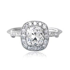 Beautiful cushion cut diamond in a platinum and diamond mounting. Center diamond is 1.53ct, G color, VS2 clarity and is certified by EGL. It is surrounded by a row of pave set diamonds and the shank is accented with 4 pave set diamonds on each side.