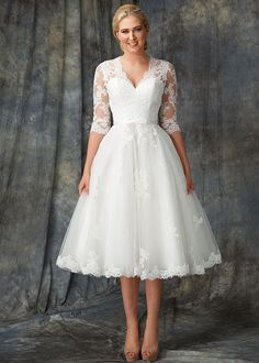 Elvina is the perfect tea-length gown for any bride who wants to look modern but preserve every touch of elegance on her special day. Detailed with delicate lace fabric, Elvina features ¾ length sleeves and a modest V-Neckline. The tea-length skirt is scattered with hand-beaded lace appliqués and features a lace trim detail on the hem edge - Wedding Dress by Berketex Bride