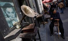 A woman rests next to an antique music player on display for sale at Panjiayuan flea market in Beijing, China, April 14, 2012. (Vincent Thian/Associated Press) #