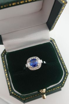 Surrounded by a cluster of round and baguette cut diamonds, the blue sapphire in this engagement ring is a deep blue. This is a unique Art Deco style design and features a decorative millegrain edging around the gemstones. #BlueSapphireRing #SapphireRing #LondonVictorianRing #ClusterEngagementRing #DeepBlueSapphire #ArtDecoStyle Platinum Diamond Rings, Blue Sapphire Rings, Sapphire Diamond, Diamond Cuts, Diamond Cluster Engagement Ring, Designer Engagement Rings, Deep Blue, Baguette, Unique Art