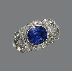 SAPPHIRE AND DIAMOND RING, CIRCA 1925 Set with a cushion-shaped sapphire measuring approximately 8.6 by 7.7 by 5.5 mm., within a scallop-edged frame decorated with 34 round, single-cut, triangle-shaped and baguette diamonds, mounted in platinum