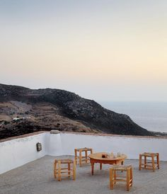 The rooftop terrace of Stefania Mansion, one of Katerina Tsigarida's restored houses in Patmos, with traditional, locally produced Greek rush seats and a view to Profitis Ilias mountain, Kipi Bay and the southwest side of the island.