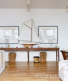 A handsome model sailboat grounds a sea-themed vignette in the great room.  | Photographer: Virginia Macdonald Designer: Montana Burnett