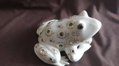 This little guy has gold leaf accents with clear and green crystals. He is holding a diamond that is made of crystal. Lovely frog to add to your collection