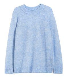 Lichtblauw gemêleerd. Een gebreide trui van zachte kwaliteit waarin wol en mohair zijn verwerkt. De trui heeft raglanmouwen en een ribgebreide boord langs