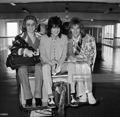 Members of The Faces on a luggage cart at London Airport (from left) Kenny Jones, Ron Wood and Rod Stewart. 1974