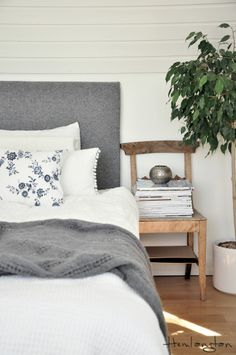 Bedroom in white, grey and blue. Wood tone makes for a richer look