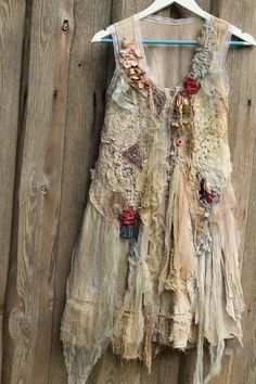Long feminine floaty cotton vest in refined shades, with bohemian flair of tattered laces and tulles and intricate details. Lightweight and floaty piece has been hand dyed in uneven shades of cream, beige, pale gray; reworked with antique laces and antique silk appliques. The bottom edge