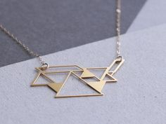 tangram necklace This pendant was inspired by the chinese wooden Tangram puzzles the pendant is made of brass and plated in 24 K gold. It