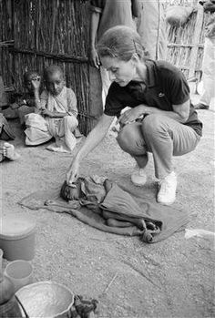 "Audrey Hepburn visits with a severely malnourished child in Baidoa, the site of mounting relief efforts. ""For many it's too late, but for many, many more we can still be on time,"" said Ms. Hepburn, after witnessing the impact of famine on Somalia's children in 1992"