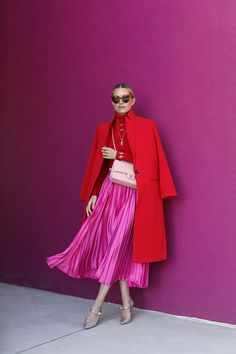 Blair Eadie wearing a red and pink fall outfit featuring a bright pleated skirt // Click through for more skirt outfits and colorful fall looks on Atlantic-Pacific