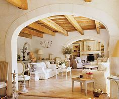 Rough hewn beams and fantasically large limestone or plastered (typical French) arches characterize this relaxed Provencal home.  Linen slipcovered sofas are punctuated with distressed tables and garden architecural pieces.