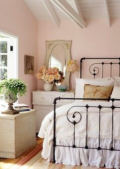 Black iron bed looks crisp and modern in the frilly pink room