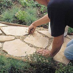 Install this flagstone path in a weekend, with this tutorial from 'Sunset'. Keep the cost down by just making a portion of the path flagstone, and the rest pea gravel.