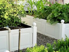 Raised garden beds using garage door panels/shudders and vinyl fence posts.