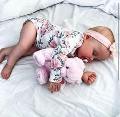 Sleeping baby girl with pink teddy, pink headband, and adorable floral onesie