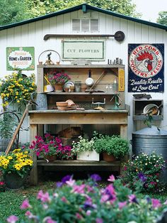Turn a ho-hum garage or shed into a work of art by adding a collection of your favorite vintage items. Here, the back of a garage gets a face-lift with a pretty and practical potting bench, old garden tools, metal advertising signs, and pots of colorful flowers