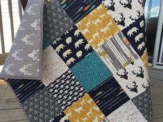 This adorable deer themed quilt features, deer, buck silhouette, wolves, arrows, and geometric prints in navy, gray, yellow, and teal. Two