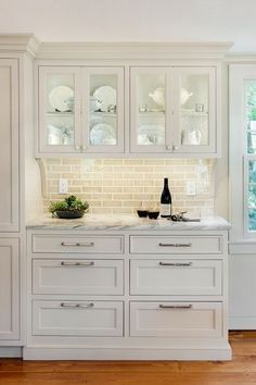 white cabinetry, marble countertops, backsplash, glass cabinets --- bar