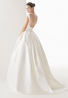 Simple, clean and modern. This two-piece wedding dress has a fitted boat neck, sleeveless top with a low, open back and princess skirt, and is belted at the natural waist and finished with a bow.