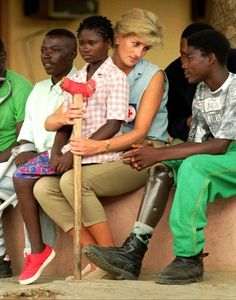Diana, Princess of Wales, talks to amputees, in this Tuesday January 14, 1997 file photo, at the the Neves Bendinha Orthopedic Workshop on the outskirts of Luanda, Angola. Sitting on Diana's lap is 13-year-old Sandra Thijica who lost her left leg to a land-mine while working the land with her mother in Saurimo, eastern Angola, in 1994. Princess Diana is visiting Angola in an effort to create awareness about land-mines. (AP Photo/Joao Silva)