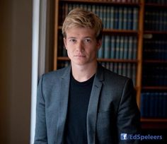 Ed Speleers in a library...