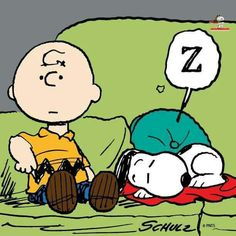 Snoopy sleeping on the couch next to Charlie Brown.