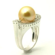 An unusual but nevertheless very beautiful design comes with this intriguing Golden South Sea Pearl & Diamond Engagement Ring stamped in 18k White Gold featuring a clean Golden Pearl set on the top of the ring surrounded by additional White Round accent side stones on the very unique shank. This Golden South Sea Pearl ring …