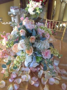Wedding centerpiece of peach roses, blush roses, pink roses, cream stock, peach stock, pink stock, white hydrangea, mini green hydrangea  and seeded eucalyptus in a white urn