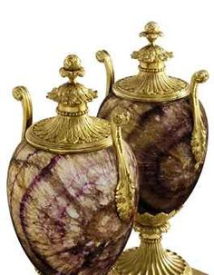 A PAIR OF GEORGE III ORMOLU-MOUNTED BLUE JOHN CANDLE VASES BY MATTHEW BOULTON, CIRCA 1775 Each surmounted by a removable top with pine-cone finial above a spreading domed acanthus base and pearled neck, the top reversing to form a baluster-shaped stiff-leaf candle-nozzle with removable drip pan, the ovoid body with reeded rim flanked by scrolled handles cast with rosettes, husk trails and acanthus sprays, above an acanthus cup and fluted spreading circular socle with laurel collar & square… Antique Art, Antique Silver, Castleton Derbyshire, Candle Vases, John Stones, Acanthus, Ancient Art, Pottery Art, Art Decor