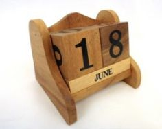Hand Crafted Wooden Perpetual Desktop Calendar.   Hand crafted in Thailand from monkey pod wood. Each calendar is crafted with a wooden frame with the blocks sitting inside. There are two large cubes with numbers on and three smaller long blocks below with the months of the year on. The blocks can be changed around by removing them and then placing back inside the frame
