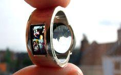 fotografía de manos sosteniendo un anillo con proyector y reflejando una imagen de una pareja