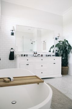 This renovated original 1930's estate in Bowral in the Southern Highlands is complete with a white weatherboard façade, impeccably styled spaces, original fireplaces, antique tapware, white and charcoal bathroom, and light-filled sunroom adorned with hanging planters 1930s Bathroom, The Secret