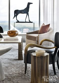 A corner of the living room commands attention thanks to sculptural details including a Moulthrop bowl, horse sculpture and curved horn chair.
