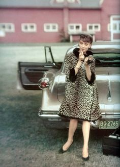Model standing in front of a Chrysler Le Baron for Vogue, October 1, 1959.