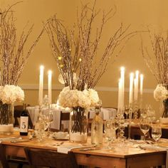 different glass candle holders grouped together.  flowers - could be done without the sticks in the flowers