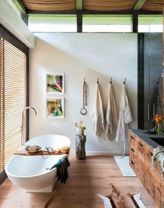 So organic and whimsical.  I like the old stump for side table or stool; the organic cotton towels, the wood floors.  But what is that hanging on the wall-- dog collar and leash?