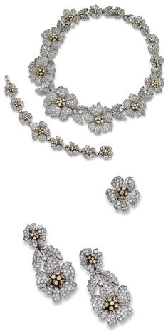 DIAMOND SUITE.   The articulated garland of floral and foliate inspiration set with brilliant-cut diamonds, the pistils set en tremblant, highlighted by similarly-cut stones of yellow tint; a bracelet, a pair of pendent earrings and a ring en suite, mounted in white gold