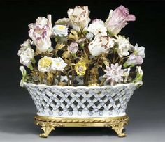 AN ORMOLU-MOUNTED MEISSEN BASKET FITTED WITH A BOUQUET OF FRENCH SOFT- PASTE PORCELAIN FLOWERS THE MEISSEN BASKET CIRCA 1750 WITH BLUE CROSSED SWORDS MARK, THE FLOWERS FRENCH 18TH CENTURY, THE ORMOLU 19TH CENTURY