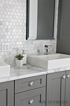 Formica 180FX Calacatta marble laminate countertop, hexagon mosaic marble backsplash and Chelse Gray vanity in ensuite bathroom with raised sinks by Kylie M Interiors