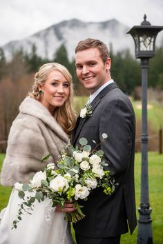 Bride in gray fur wrap and emerald teardrop earrings and groom in dark suit with white boutonniere.