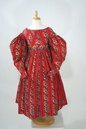 The huge gigot sleeves on this vibrant polychrome roller printed cotton child's dress date it squarely in the romantic era, mid 1830s, when sleeves were at their fullest.