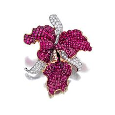 A ruby and diamond brooch designed as an orchid, set with calibré-cut rubies and pavé-set diamonds; estimated total diamond weight: 2.50 carats; mounted in eighteen karat gold and platinum; length: 2 1/2in.