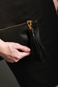 "Big enough to use for a nighttime clutch and small enough to tuck into your  daytime purse, our signature pochette belongs with you at all  times. Lined in Stewart tartan and finished with bright gold hardware, this  smart-phone friendly size means you won't have to leave anything out (or  behind) again. A removable 5"" leather tassel zipper pull lends a note of  interest without being flashy.      * 5"" W x 7"" L     * Leather.     * Lined.     * Made in Los Angeles"
