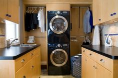 Beautifully organized Laundry Room. Plenty of space to separate everyone's clothes, iron and fold. But I think having the washer and dryer set up like that would be difficult for shorter people.